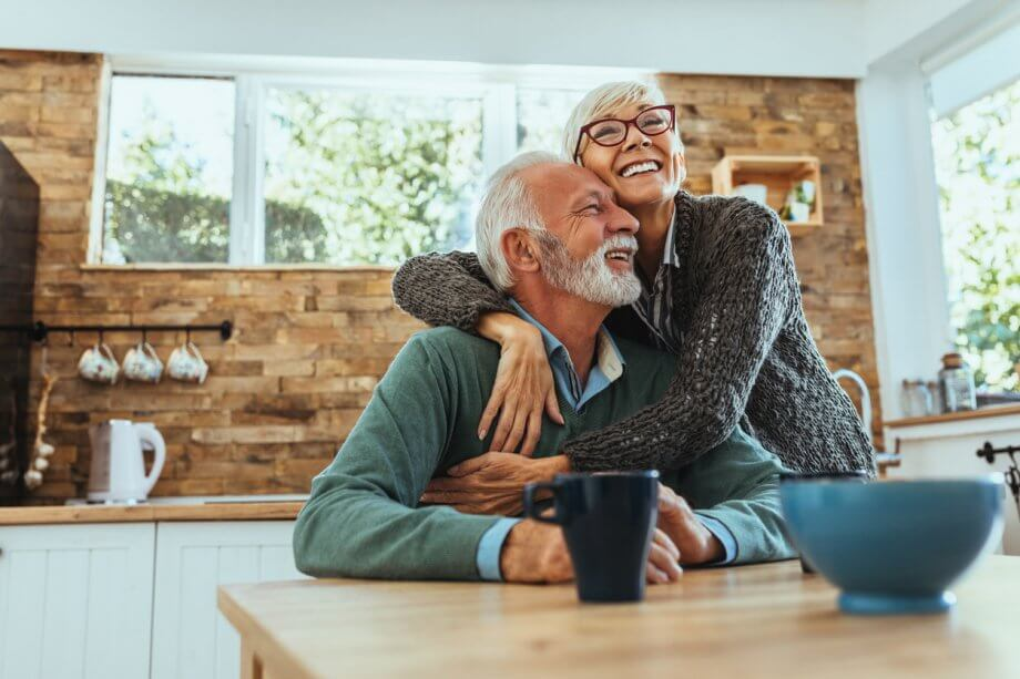 Older couple holding each other and smiling while sitting in a kitchen.
