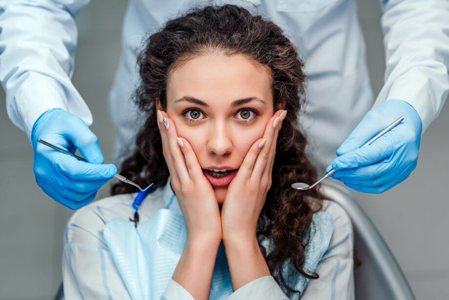 Woman with long curly brown hair scared of the dentist as the dentist stands behind her holding tools.
