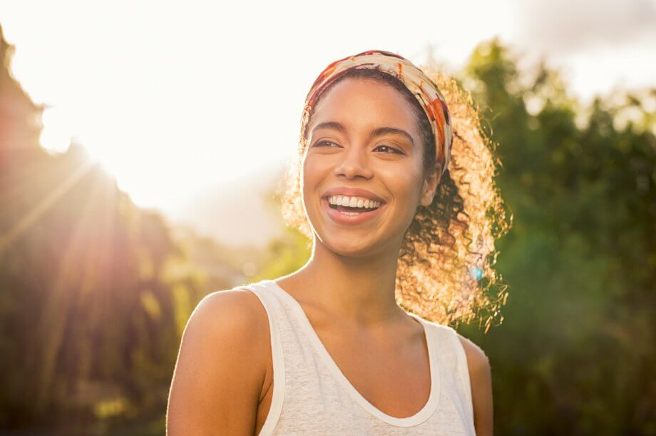 Woman smiling wearing a tank top in nature with the sun setting behind her.