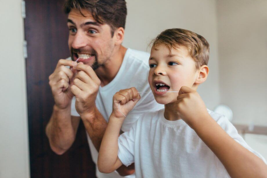 Father and Son Flossing Their Teeth